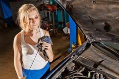 La ragazza controlla il livello di olio nell'automobile Fotografia Stock