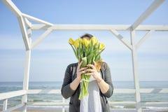 La ragazza copre il suo fronte di tulipani gialli fotografia stock libera da diritti