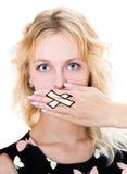 La ragazza copre la sua bocca di mano immagine stock