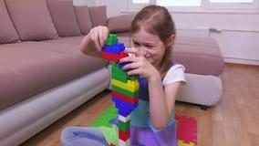 La ragazza costruisce un'alta torre dai mattoni del giocattolo