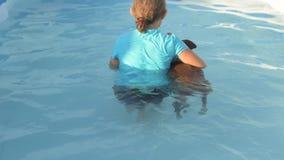 La ragazza in costume da bagno sta nuotando in chiara, acqua blu dello stagno con il maiale rosso della razza del duroc 2019 anni stock footage