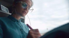 La ragazza creativa si siede sul davanzale ascolta musica, assorbe il taccuino Immagini Stock Libere da Diritti