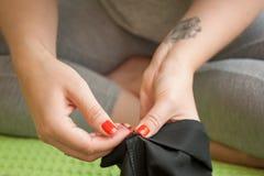 La ragazza cuce i pantaloni degli uomini Immagini Stock