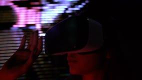 La ragazza in cuffia avricolare del vr gioca il gioco di orrore, scene di letsplay visualizzato su fondo archivi video