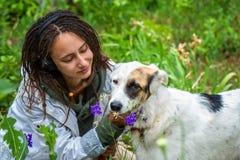 La ragazza in cuffie abbraccia un cane Ragazza del latino dell'aspetto con i dreadlocks che portano una giacca a vento bianca Alb immagini stock libere da diritti