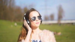 La ragazza in cuffie del bluetooth, canta e balla fuori Una ragazza dolce con capelli lunghi e ballare e sudore degli occhiali da video d archivio