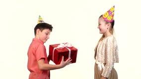 La ragazza dà ad un ragazzo il rosso del regalo I tipi baciano ciascuno archivi video