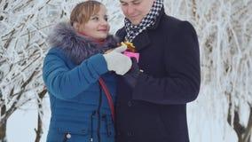 La ragazza dà al tipo un regalo Giovani coppie in un parco con il presente il concetto di amore e delle relazioni archivi video