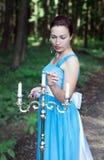 La ragazza dà fuoco tre candele su un candeliere d'argento in una foresta Fotografia Stock