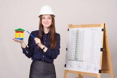 La ragazza dà una presentazione di nuova costruzione multipiana Fotografie Stock Libere da Diritti