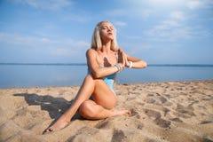 La ragazza dai capelli lunghi bionda in un vestito blu è allungante e facente l'yoga su una spiaggia adorabile al sole del sol le Immagini Stock Libere da Diritti