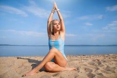 La ragazza dai capelli lunghi bionda in un vestito blu è allungante e facente l'yoga su una spiaggia adorabile al sole del sol le Fotografie Stock