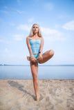 La ragazza dai capelli lunghi bionda in un vestito blu è allungante e facente l'yoga su una spiaggia adorabile al sole del sol le Fotografia Stock Libera da Diritti