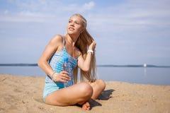 La ragazza dai capelli lunghi bionda in un vestito blu è allungante e facente l'yoga su una spiaggia adorabile al sole del sol le Fotografia Stock