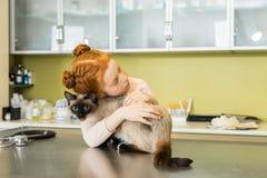La ragazza dai capelli rossi abbraccia il suo gatto alla clinica veterinaria immagini stock