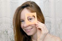La ragazza dai capelli rossi che sorride tenendo un biglietto di S. Valentino Fotografie Stock