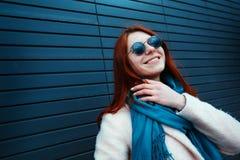 La ragazza dai capelli rossi dei pantaloni a vita bassa in occhiali da sole alla moda sta posando davanti ad una parete nera sull fotografia stock
