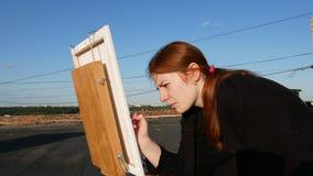 La ragazza dai capelli rossi dipinge un'immagine Sul tetto archivi video