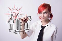La ragazza dai capelli rossi disegna un disegno della casa immagini stock libere da diritti