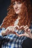 La ragazza dai capelli rossi mostra il cuore Immagini Stock Libere da Diritti