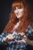 La ragazza dai capelli rossi mostra il cuore Fotografia Stock Libera da Diritti