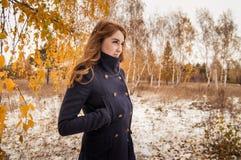 La ragazza dai capelli rossi nella foresta di autunno Immagini Stock