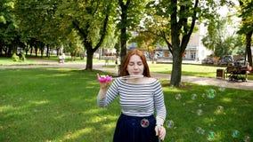 La ragazza dai capelli rossi soffia le bolle di sapone nel movimento lento del parco archivi video