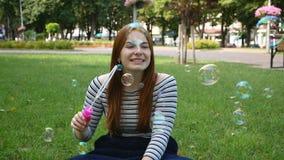 La ragazza dai capelli rossi soffia le bolle di sapone nel movimento lento del parco stock footage
