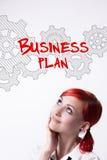 La ragazza dai capelli rossi sta elaborando un business plan Immagine Stock Libera da Diritti