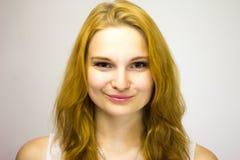 La ragazza dai capelli rossi in un rivestimento bianco sorride confuso alla macchina fotografica fotografia stock libera da diritti