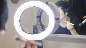 La ragazza davanti allo specchio con una spazzola fa il trucco stock footage