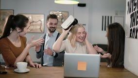 La ragazza decolla la sua realtà virtuale di vetro dopo avere utilizzato le nuove esperienze della parte di app con il gruppo nel fotografia stock libera da diritti
