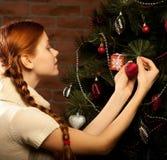 La ragazza decora l'albero di Natale Fotografia Stock