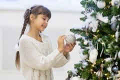 La ragazza decora l'albero di Natale Fotografie Stock