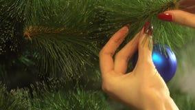 La ragazza decora l'albero di Natale e la caduta su un ramo la palla brillante blu archivi video