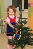 La ragazza decora una conifera. Fotografia Stock Libera da Diritti