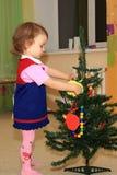 La ragazza decora una conifera. Fotografia Stock