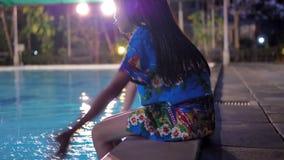 La ragazza dei bambini si siede dal lato della piscina all'aperto che spruzza i suoi piedi l'acqua nella sera archivi video