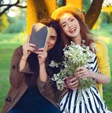 La ragazza dei pantaloni a vita bassa di modo ha letto il libro sulla natura Fotografie Stock