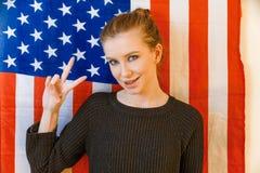 La ragazza dei pantaloni a vita bassa fa il segno di vittoria davanti alla bandiera degli Stati Uniti Fotografie Stock
