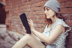 La ragazza dei pantaloni a vita bassa lavora alla compressa su Internet Fotografia Stock