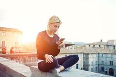 La ragazza dei pantaloni a vita bassa sta leggendo il messaggio di testo sul telefono delle cellule, mentre sta sedendosi su un t Fotografie Stock Libere da Diritti