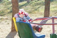 La ragazza del bambino che gioca sulla rotonda o allegro-va fotografie stock