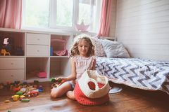 La ragazza del bambino che pulisce la sua stanza ed organizza i giocattoli di legno nella borsa tricottata di stoccaggio Fotografia Stock