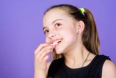 La ragazza del bambino con capelli lunghi gradisce i dolci e gli ossequi Caloria e dieta Bambino affamato Dente dolce incorreggib immagine stock