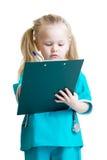 La ragazza del bambino in costume di medico prende le note isolate Fotografia Stock Libera da Diritti