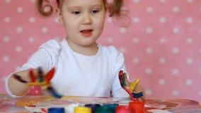 La ragazza del bambino disegna dalla spazzola e dalla pittura Arte del bambino Gouache e pitture video d archivio