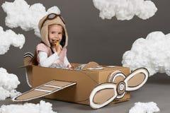La ragazza del bambino gioca in un aeroplano fatto della scatola di cartone e dei sogni di diventare un pilota, nuvole di ovatta  fotografia stock