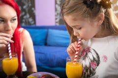 La ragazza del bambino gode di in succo d'arancia bevente Immagini Stock Libere da Diritti
