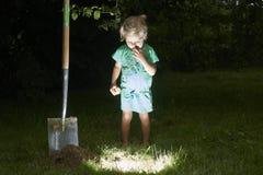 La ragazza del bambino ha dissotterrato un tesoro nell'erba Immagini Stock Libere da Diritti